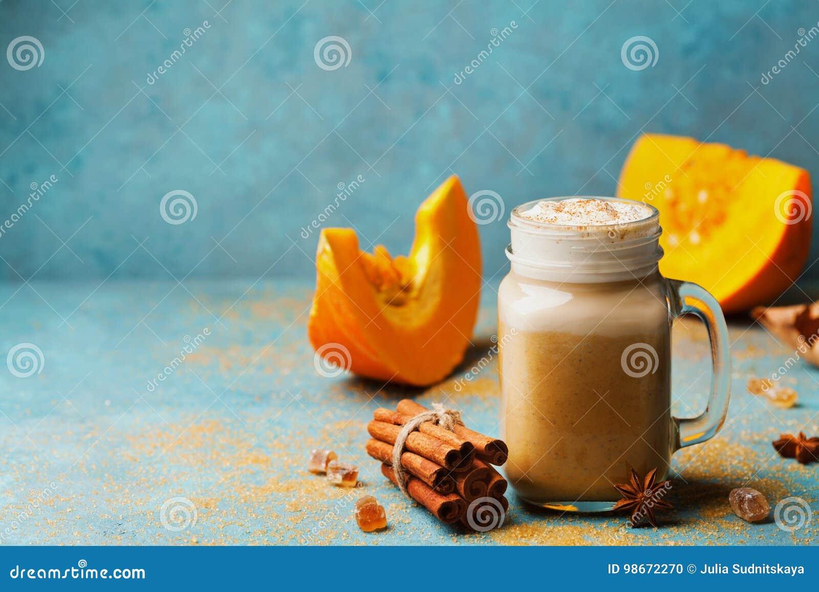 Κολοκύθα που καρυκεύεται latte ή καφές στο γυαλί στον τυρκουάζ εκλεκτής ποιότητας πίνακα Ζεστό ποτό φθινοπώρου, πτώσης ή χειμώνα