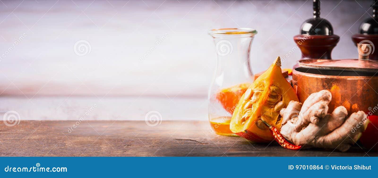 Κολοκύθα στον πίνακα γραφείων κουζινών με το μαγείρεμα του δοχείου, του ελαίου και της πιπερόριζας, μπροστινή άποψη Υπόβαθρο τροφ