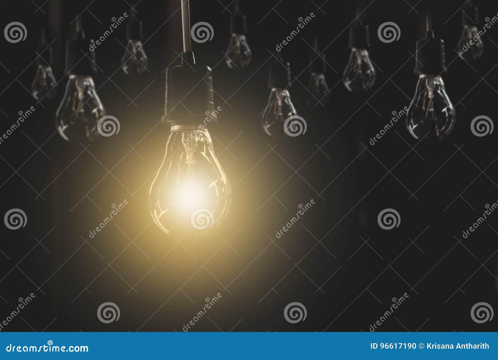 Κρεμώντας λάμπες φωτός με καμμένος μια στο σκοτεινό υπόβαθρο Έννοια ιδέας και δημιουργικότητας