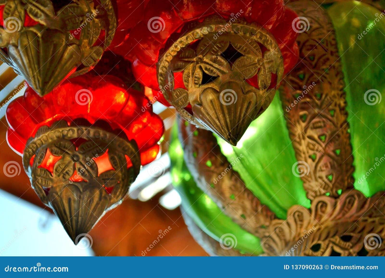 Κρεμώντας κόκκινα, πράσινα και ασημένια ζωηρόχρωμα φανάρια γυαλιού