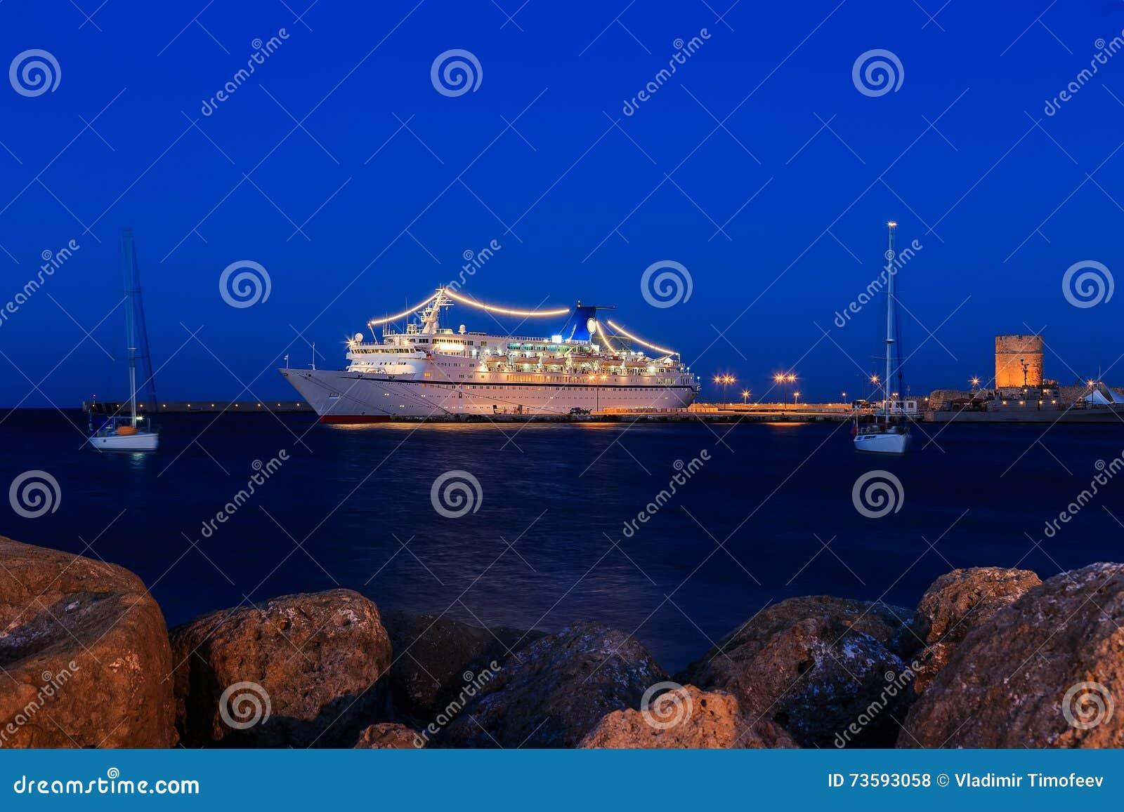 Κρουαζιερόπλοιο στο λιμένα μεταξύ του σούρουπου δύο γιοτ ναυσιπλοΐας