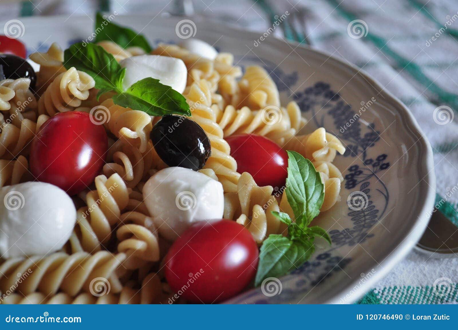 Κρύα ζυμαρικά με τη μίνι μοτσαρέλα, την ντομάτα κερασιών, τα φύλλα βασιλικού, τις μαύρα ελιές και rosé το κρασί Cerasuoloe