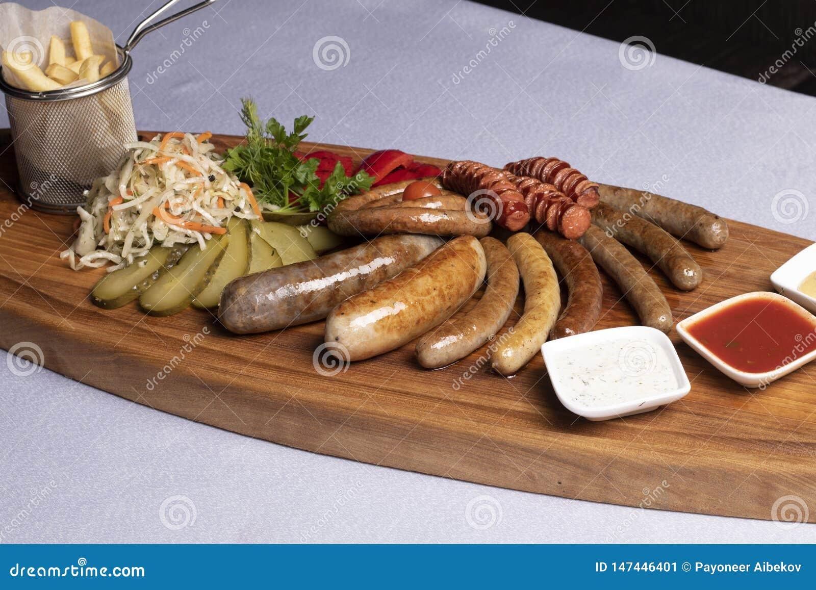 κρύα πρόχειρα φαγητά για την μπύρα, τα λουκάνικα και το τυρί με τις τηγανισμένους ντομάτες, το μαϊντανό και το κεράσι