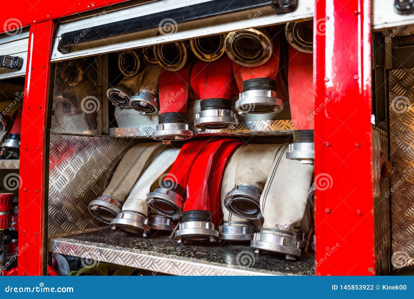 Κυλημένες μάνικες πυρκαγιάς, που τακτοποιούνται στις σειρές, στο διαμέρισμα γαντιών του πυροσβεστικού οχήματος