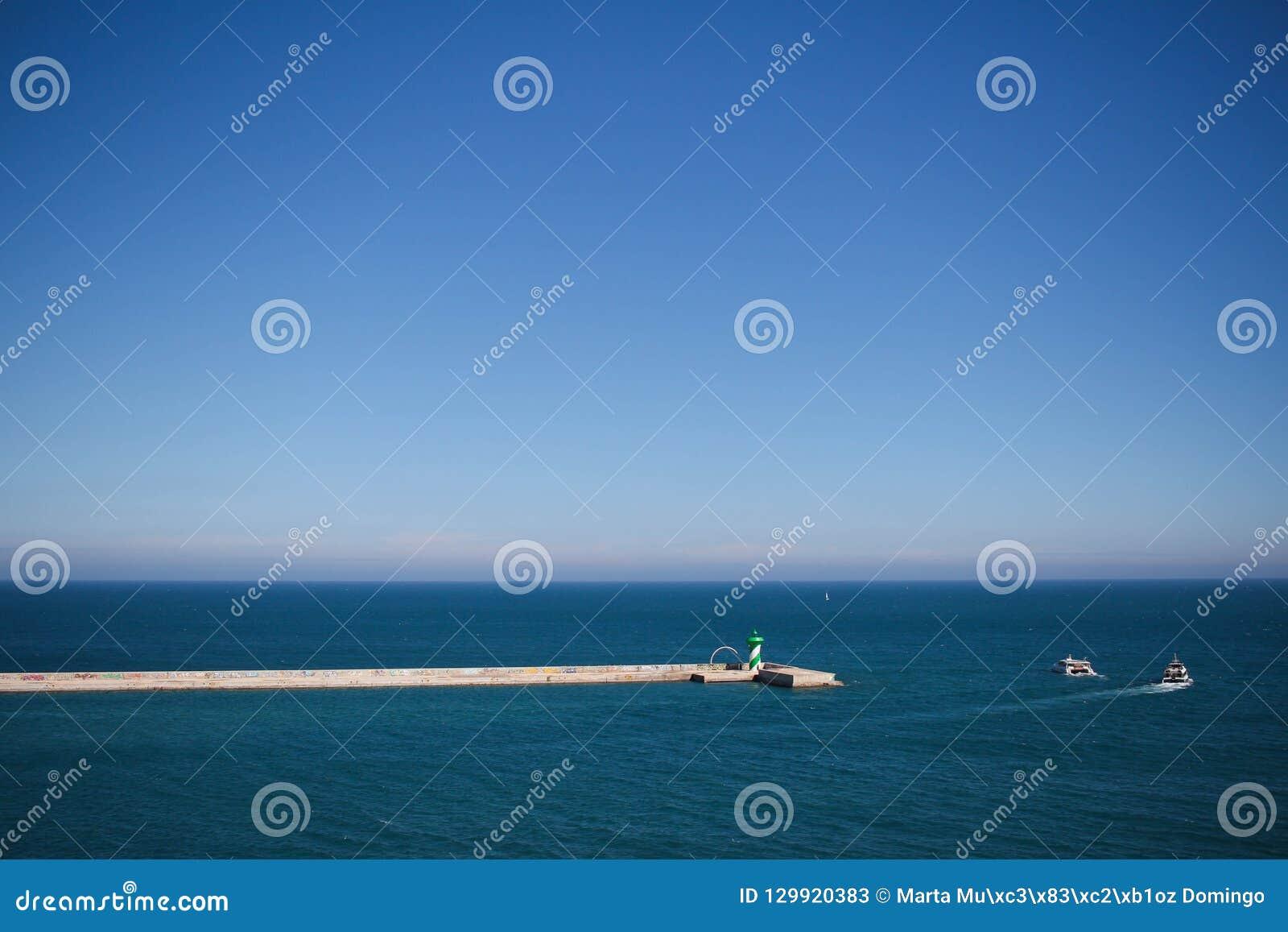 Κυματοθραύστης στο λιμένα με δύο βάρκες στο υπόβαθρο