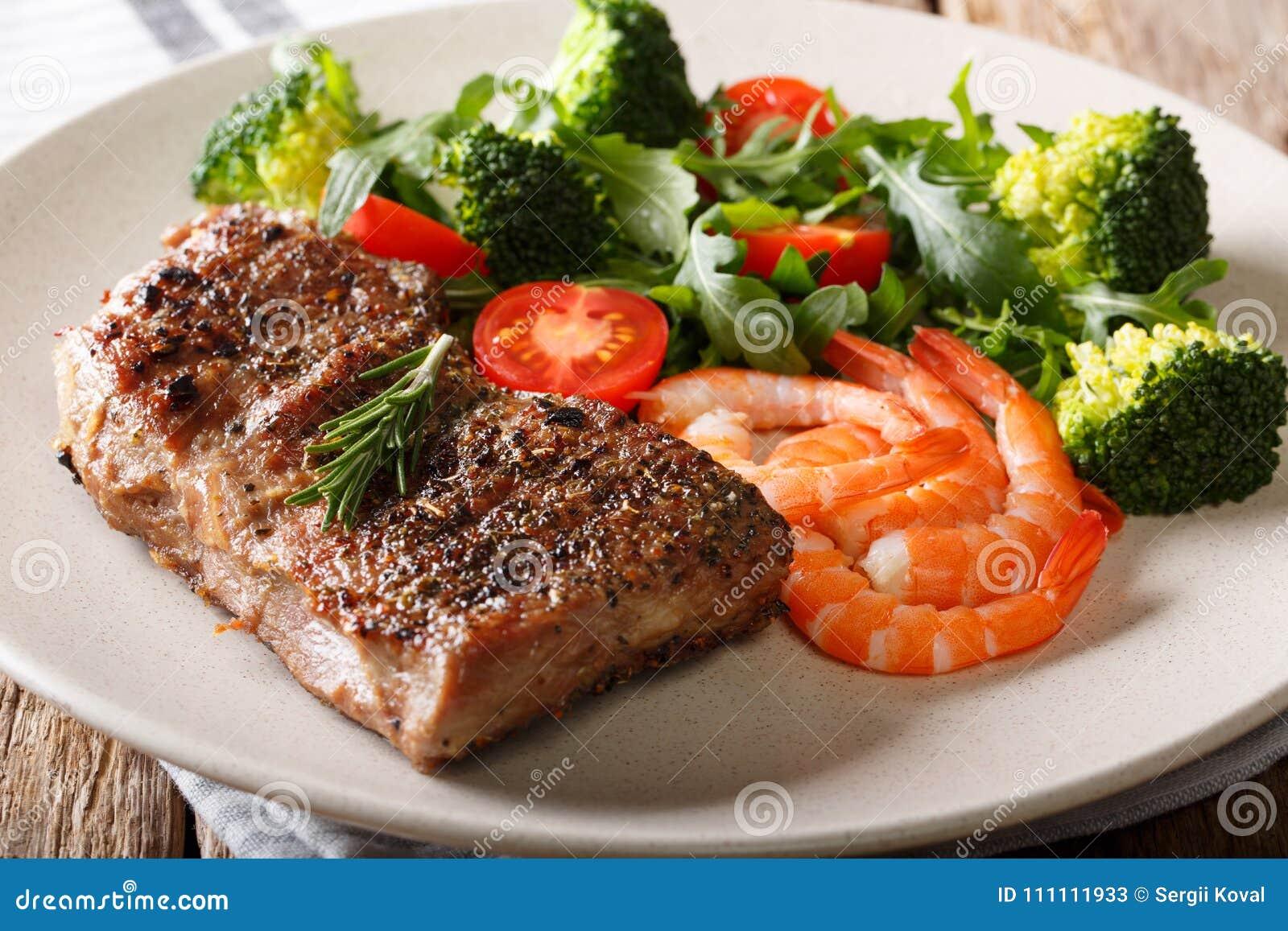 Κυματωγή και τύρφη Μπριζόλα βόειου κρέατος με τις βασιλικές γαρίδες και τα φρέσκα λαχανικά