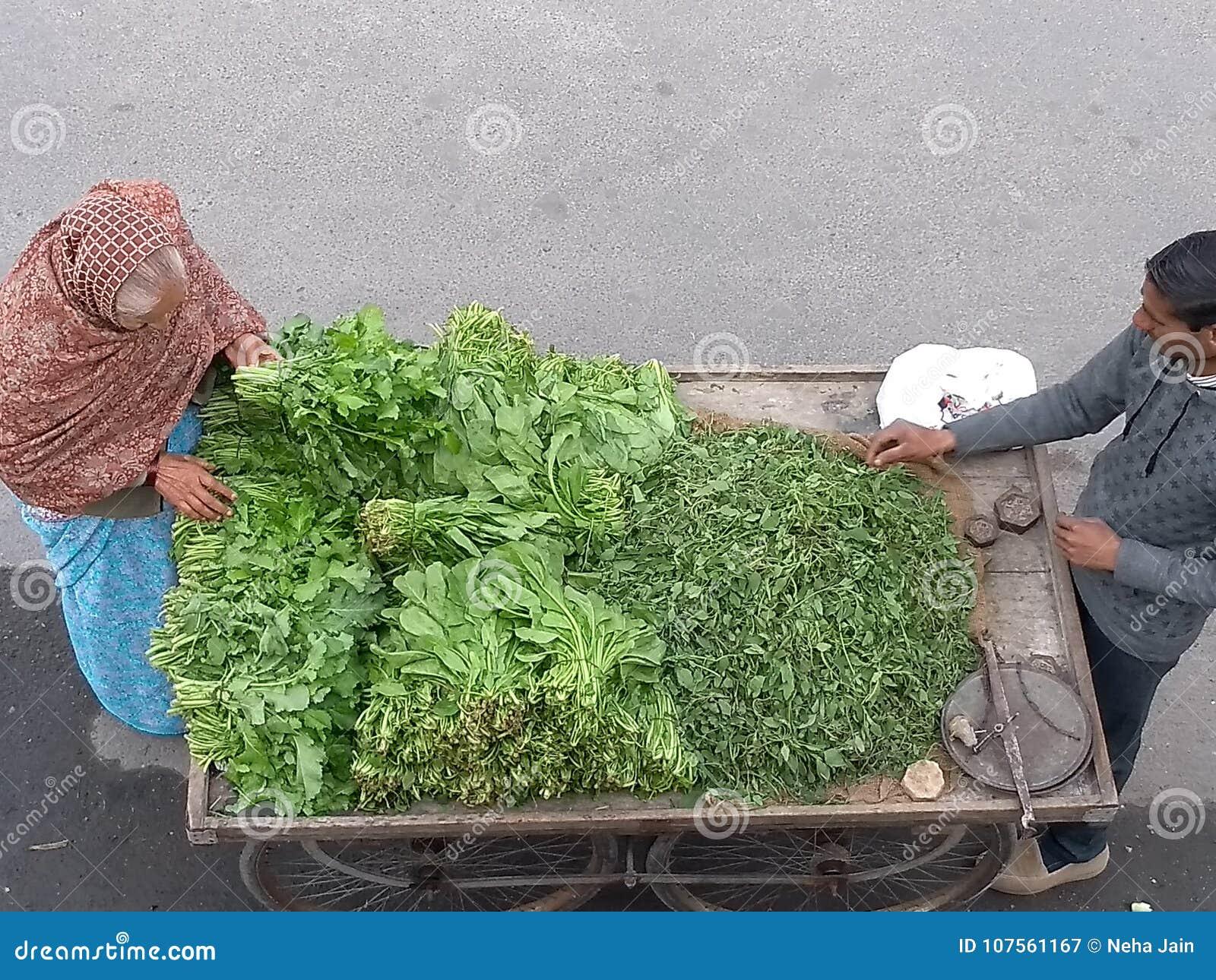 Κυρία που αγοράζει τα φυλλώδη λαχανικά