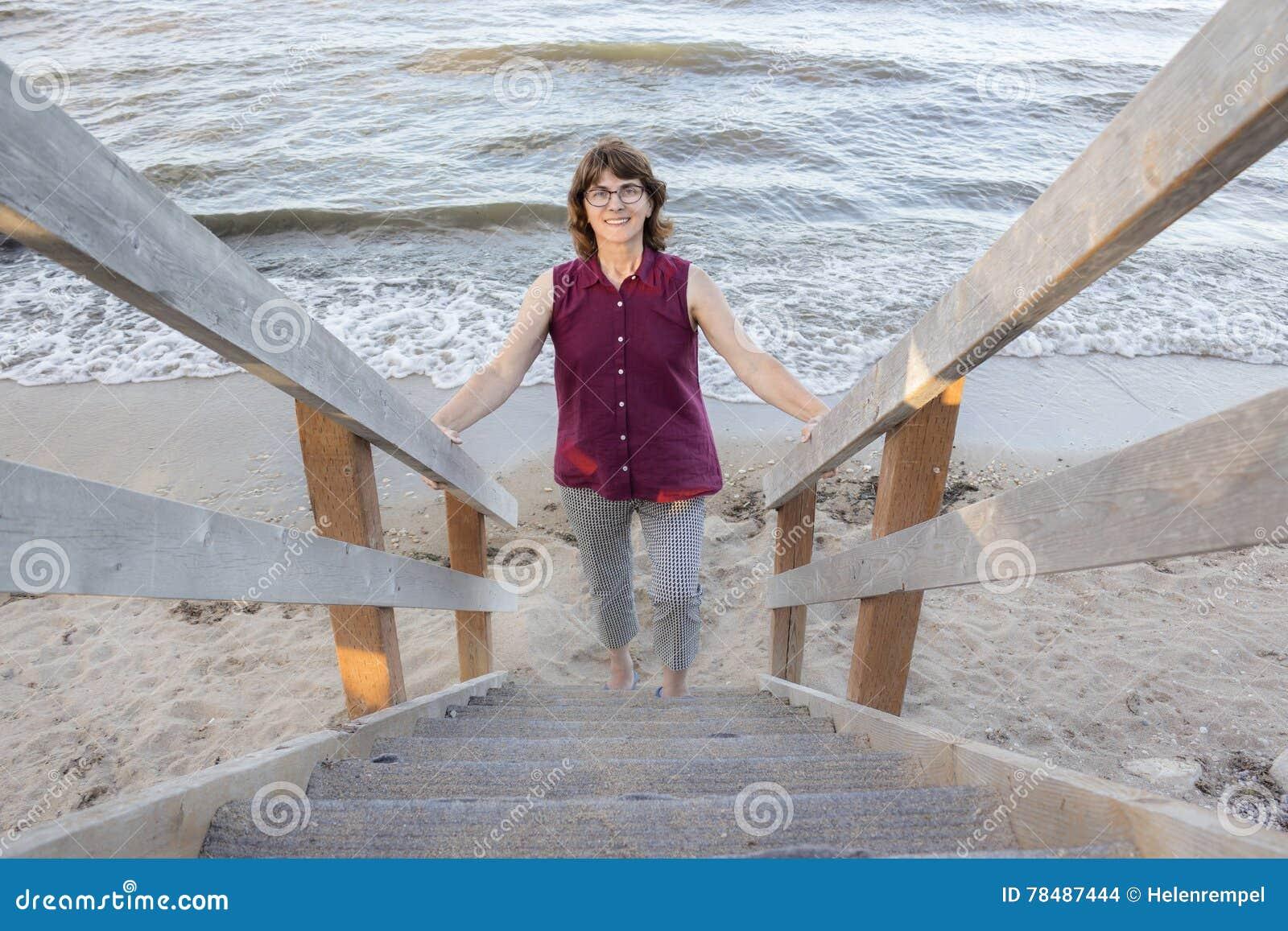 f1840790530 Κυρία που περπατά επάνω τα σκαλοπάτια από την παραλία Στοκ Εικόνες ...