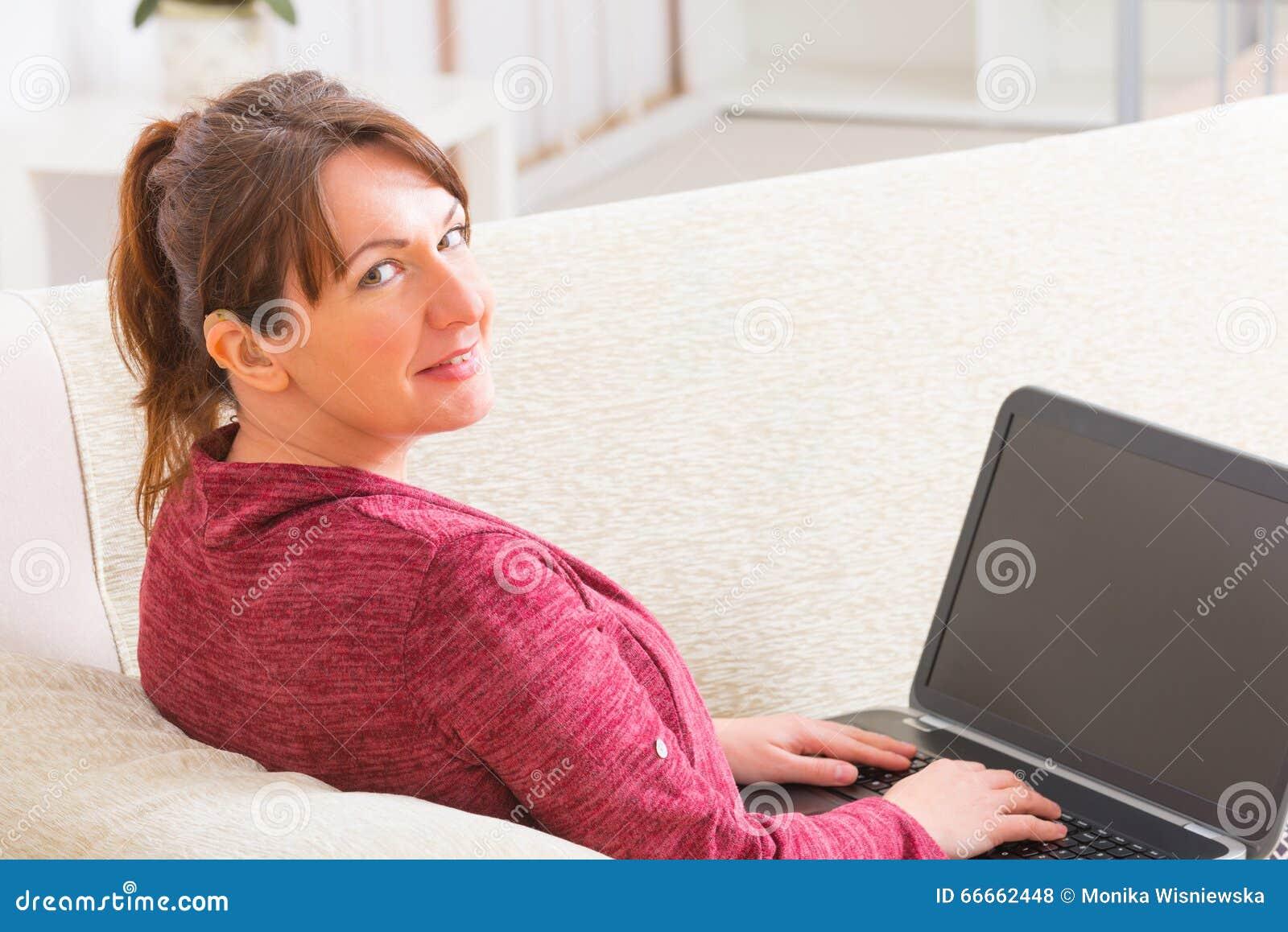 Κωφή γυναίκα που χρησιμοποιεί το lap-top στο σπίτι