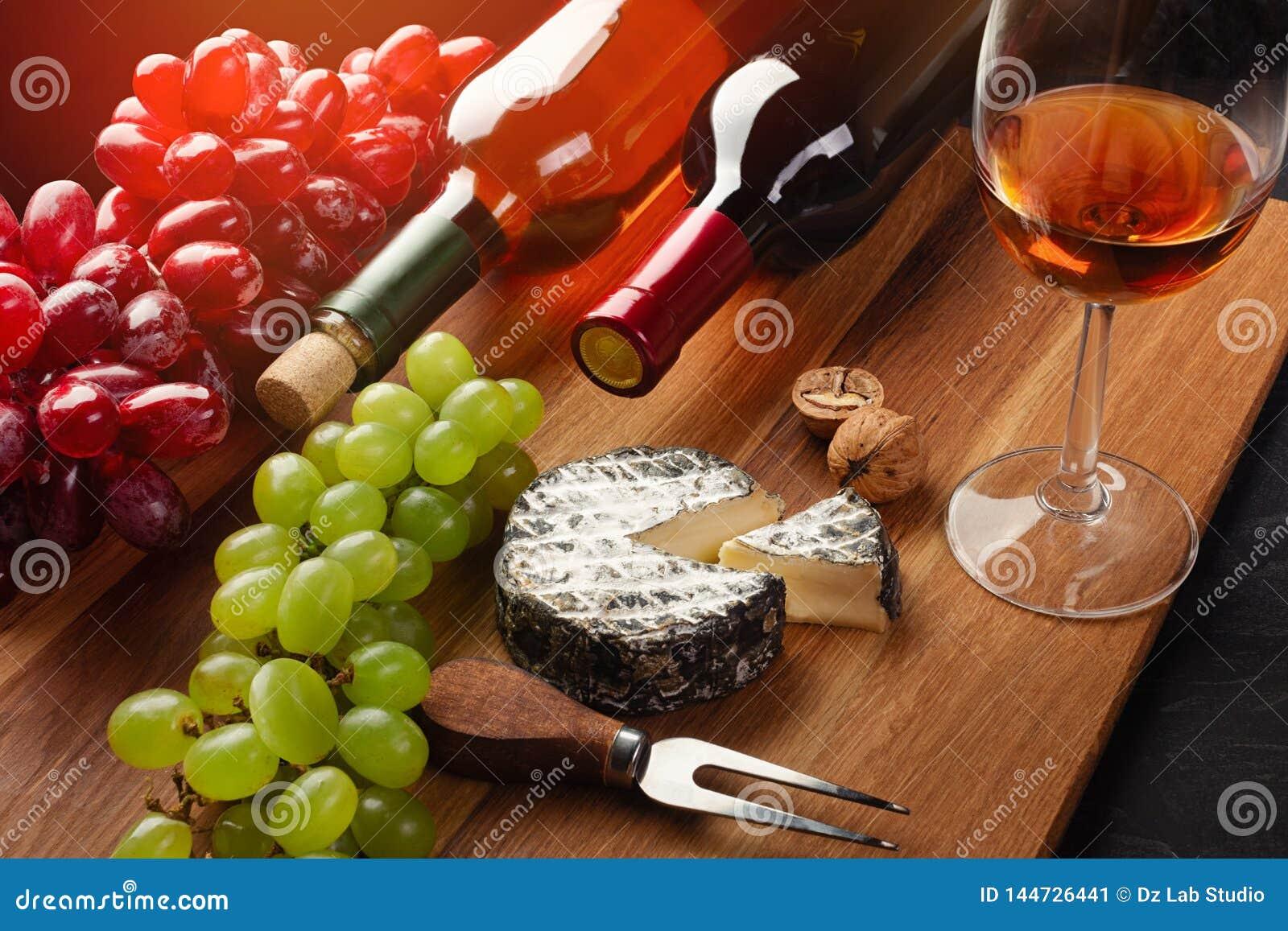 Κόκκινα και άσπρα μπουκάλια κρασιού με τη δέσμη των σταφυλιών, του κεφ