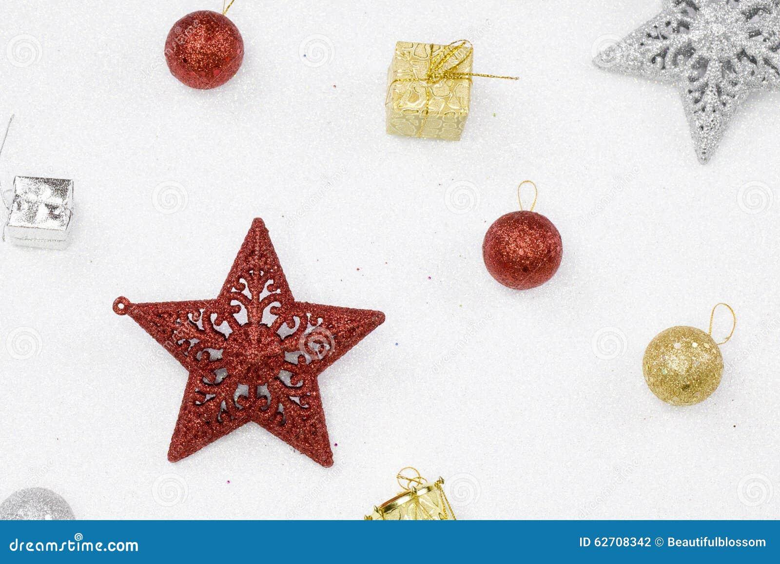 Κόκκινα και ασημένια αστέρια Χριστουγέννων με το ακτινοβολώντας άσπρο υπόβαθρο
