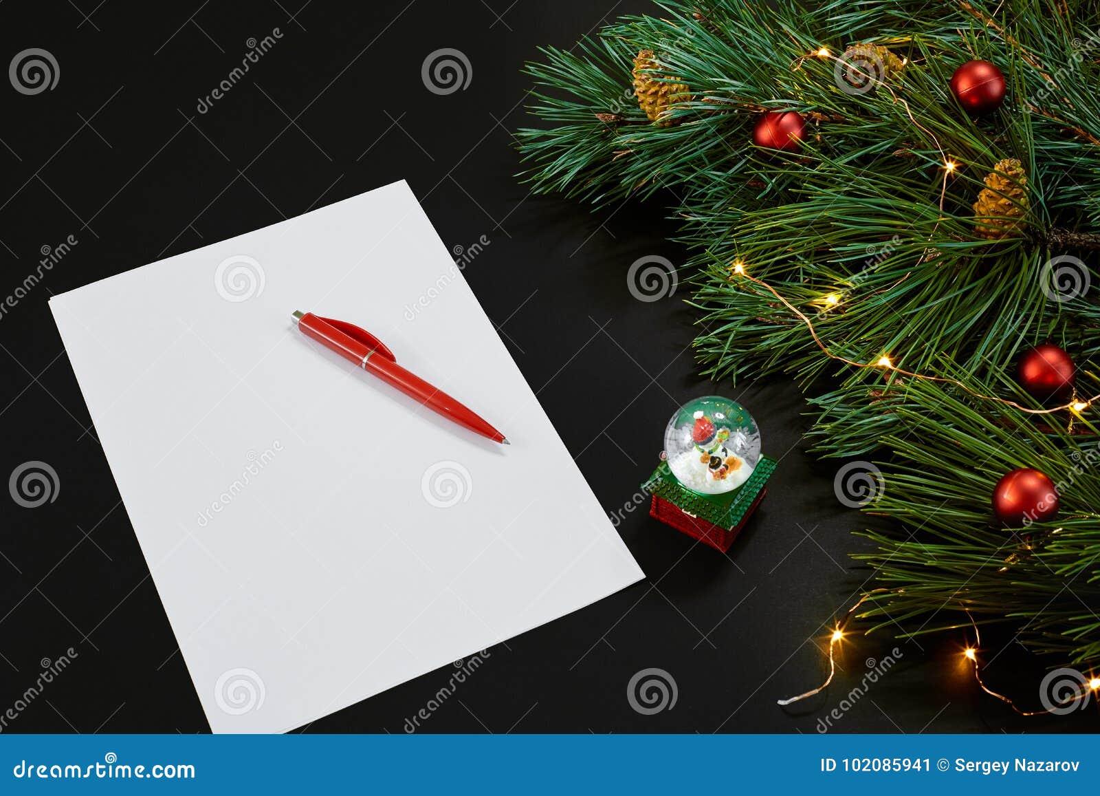 Κόκκινα σφαίρες και σημειωματάριο Χριστουγέννων που βρίσκονται κοντά στον πράσινο κομψό κλάδο στη μαύρη τοπ άποψη υποβάθρου Διάστ