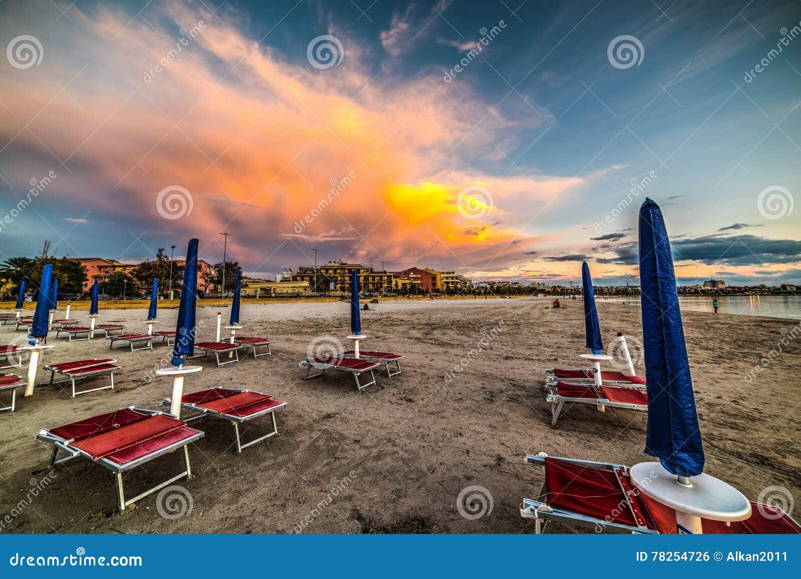 Κόκκινες καρέκλες και μπλε parasol στο σούρουπο