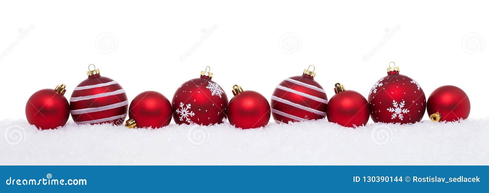 Κόκκινες μεγάλες και μικρές σφαίρες Χριστουγέννων που απομονώνονται στο χιόνι
