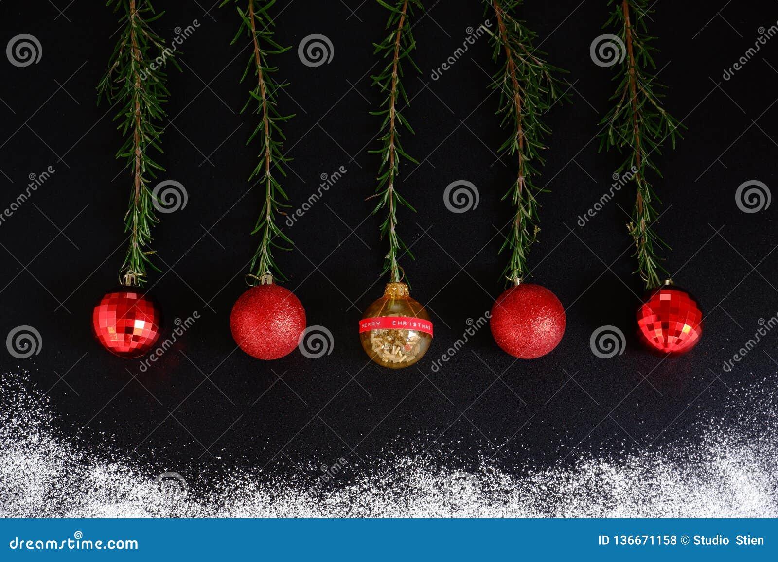 Κόκκινες σφαίρες Χριστουγέννων στο μαύρο υπόβαθρο με το χιόνι