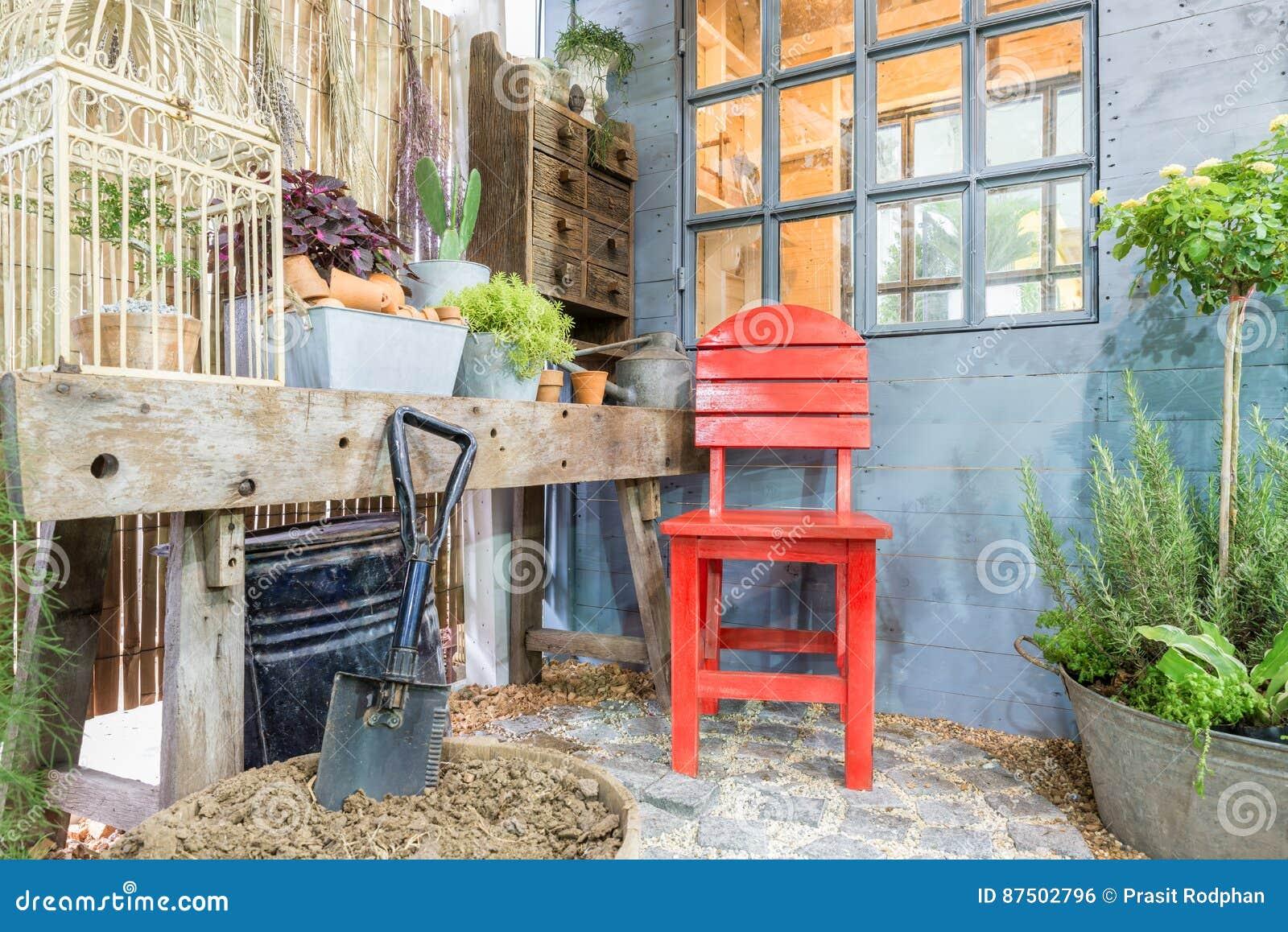 a22724f88568 Κόκκινη καρέκλα στον πράσινο κήπο με το άνετο σπίτι κήπος υπαίθριος ...
