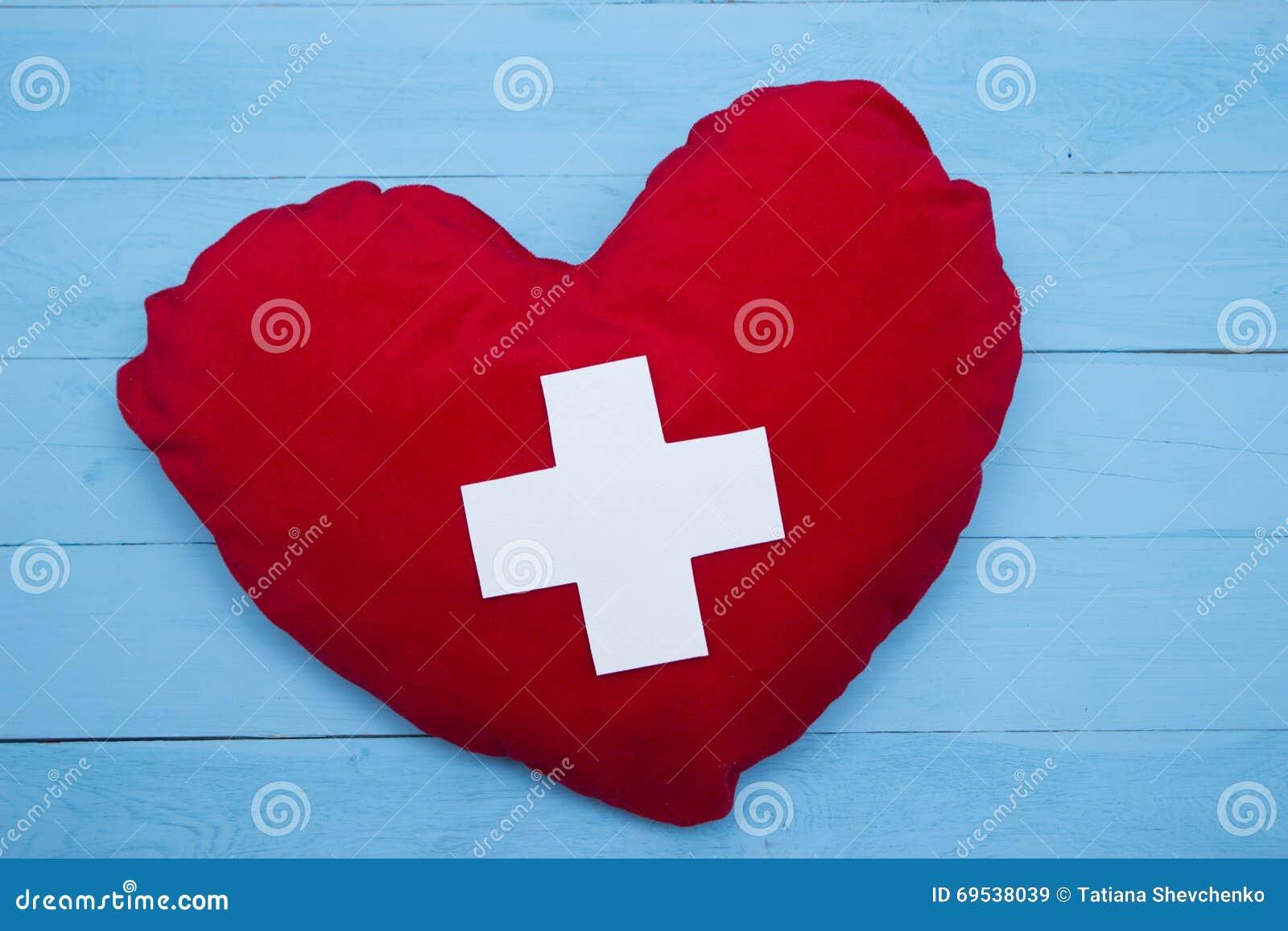 Κόκκινη καρδιά χειροποίητη με έναν άσπρο σταυρό σε ένα μπλε ξύλινο υπόβαθρο 0ddf1156eba