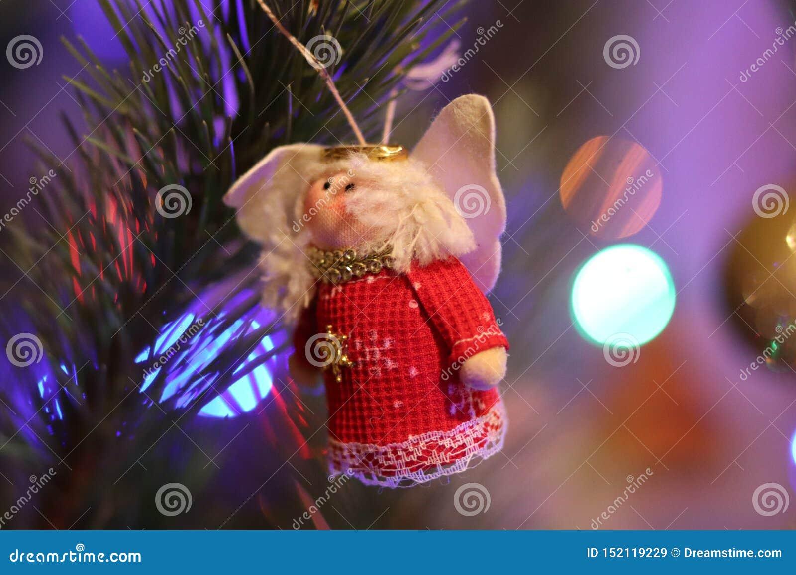 Κόκκινη κούκλα δέντρων έτους Χριστουγέννων νέα με τα φω τα Χριστουγέννων
