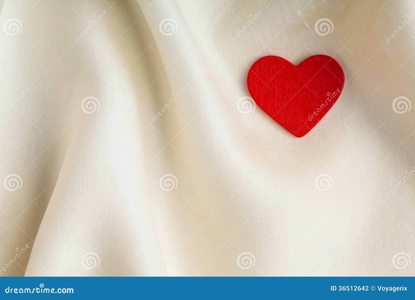 Κόκκινη ξύλινη διακοσμητική καρδιά στο άσπρο υπόβαθρο μεταξιού.