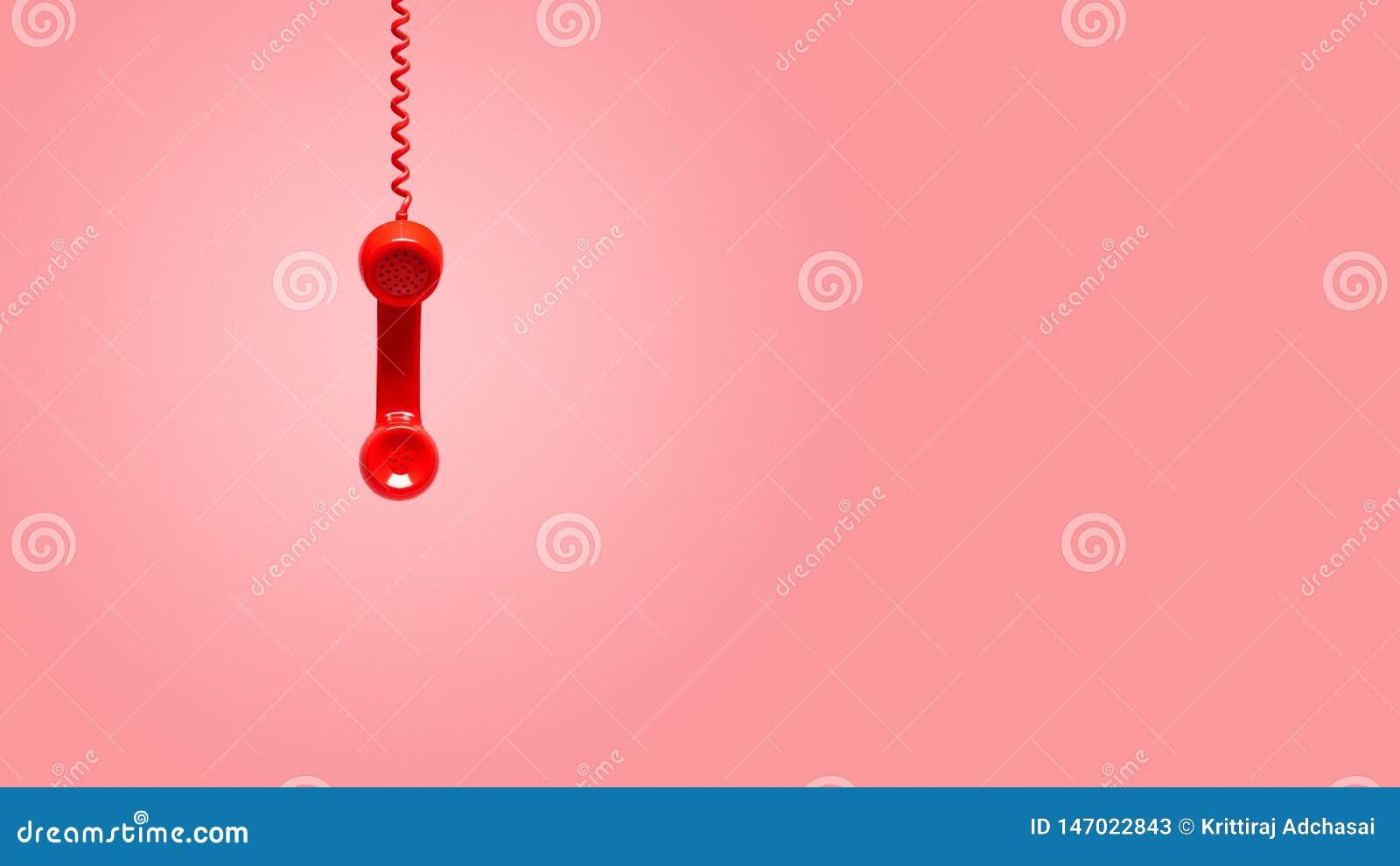 Κόκκινη παλαιά ένωση ακουστικών τηλεφώνου στο ρόδινο υπόβαθρο