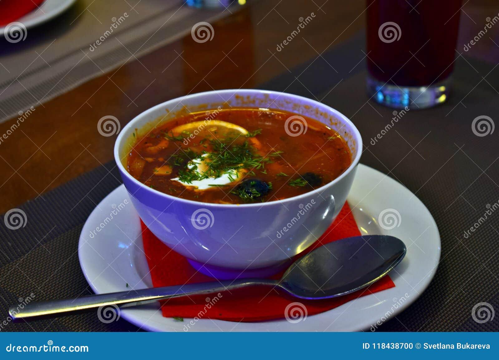 Κόκκινη πικάντικη σούπα με το λεμόνι και ελιές σε ένα άσπρο πιάτο