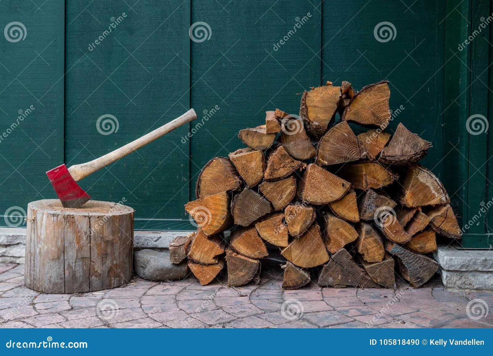Κόκκινοι τσεκούρι και σωρός του ξύλου πυρκαγιάς