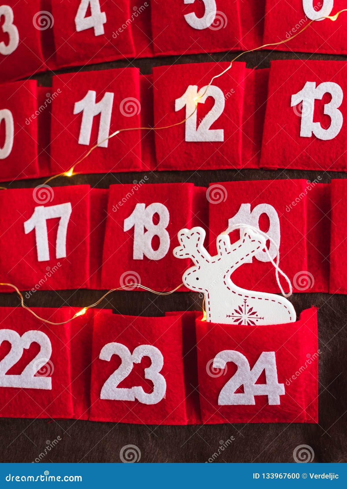 Κόκκινο ημερολόγιο εμφάνισης με την άσπρη διακόσμηση και τα φω τα ελαφιών βροχής