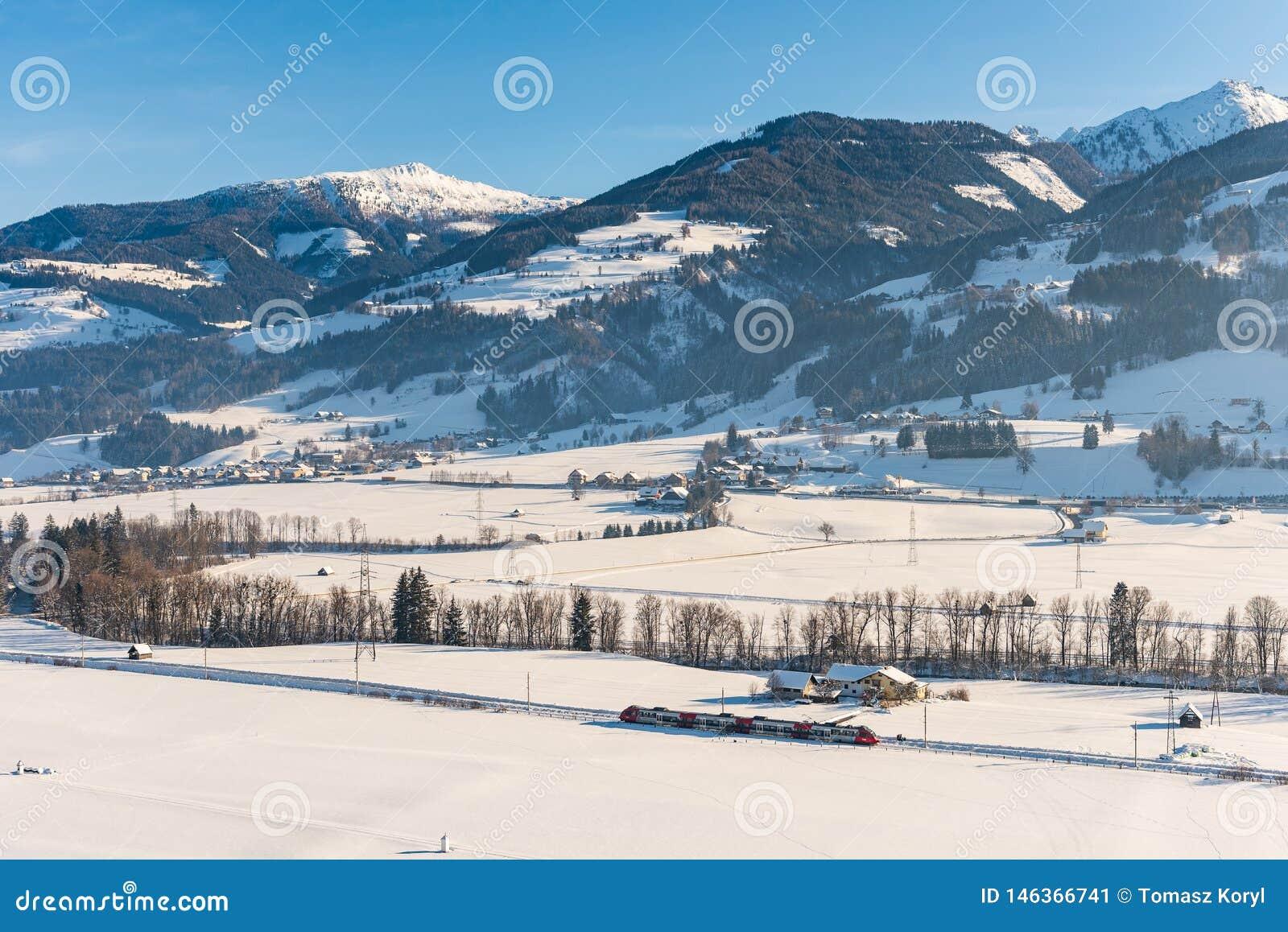 Κόκκινο και άσπρο τραίνο που περνά τους χιονισμένους τομείς σε ένα φυσικό τοπίο χειμερινών βουνών, ορεινός όγκος Dachstein, περιο