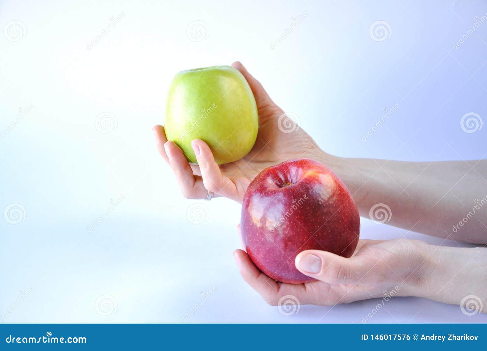 Κόκκινο και πράσινο μήλο στα χέρια στο άσπρο υπόβαθρο