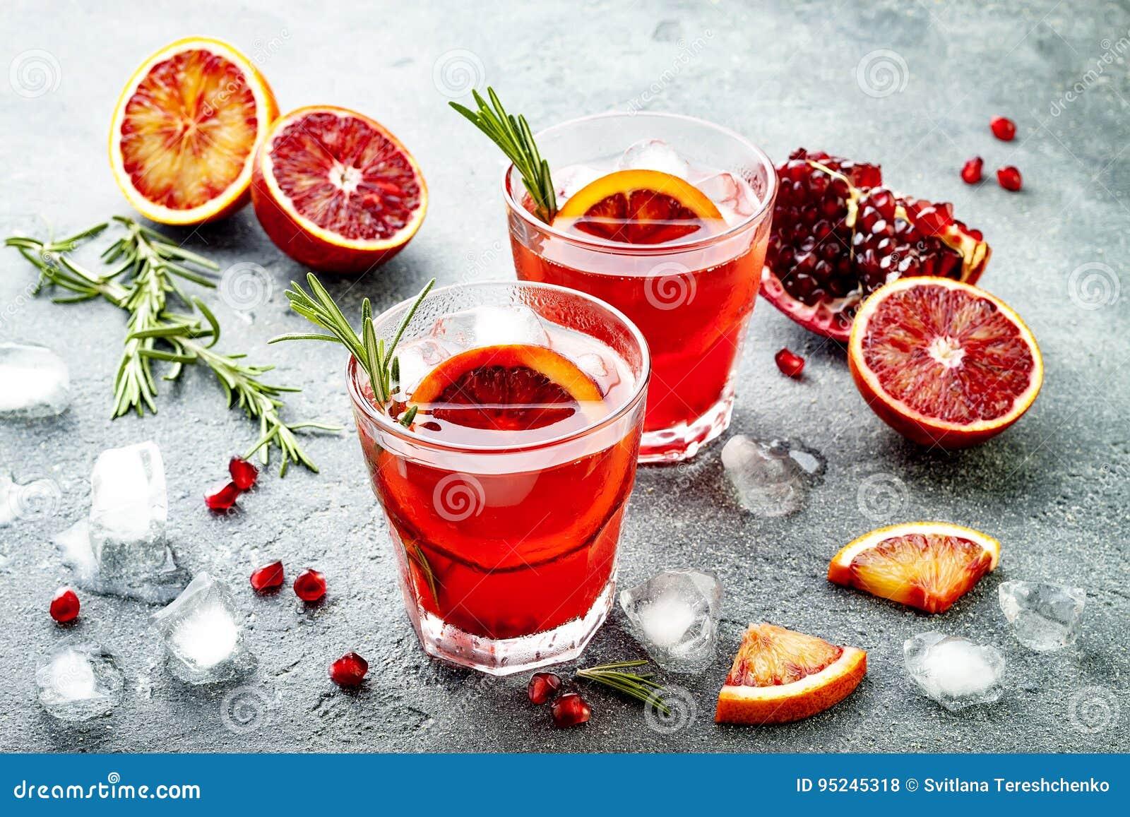 Κόκκινο κοκτέιλ με το πορτοκάλι και το ρόδι αίματος Αναζωογονώντας θερινό ποτό Απεριτίφ διακοπών για τη γιορτή Χριστουγέννων
