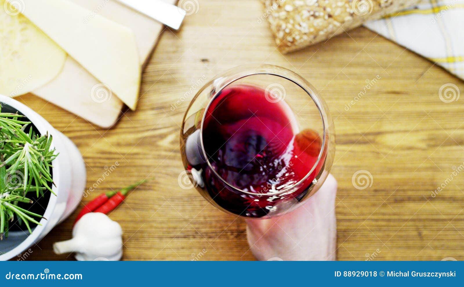 Κόκκινο κρασί που κινείται επάνω σε ένα γυαλί Holded από ένα άτομο