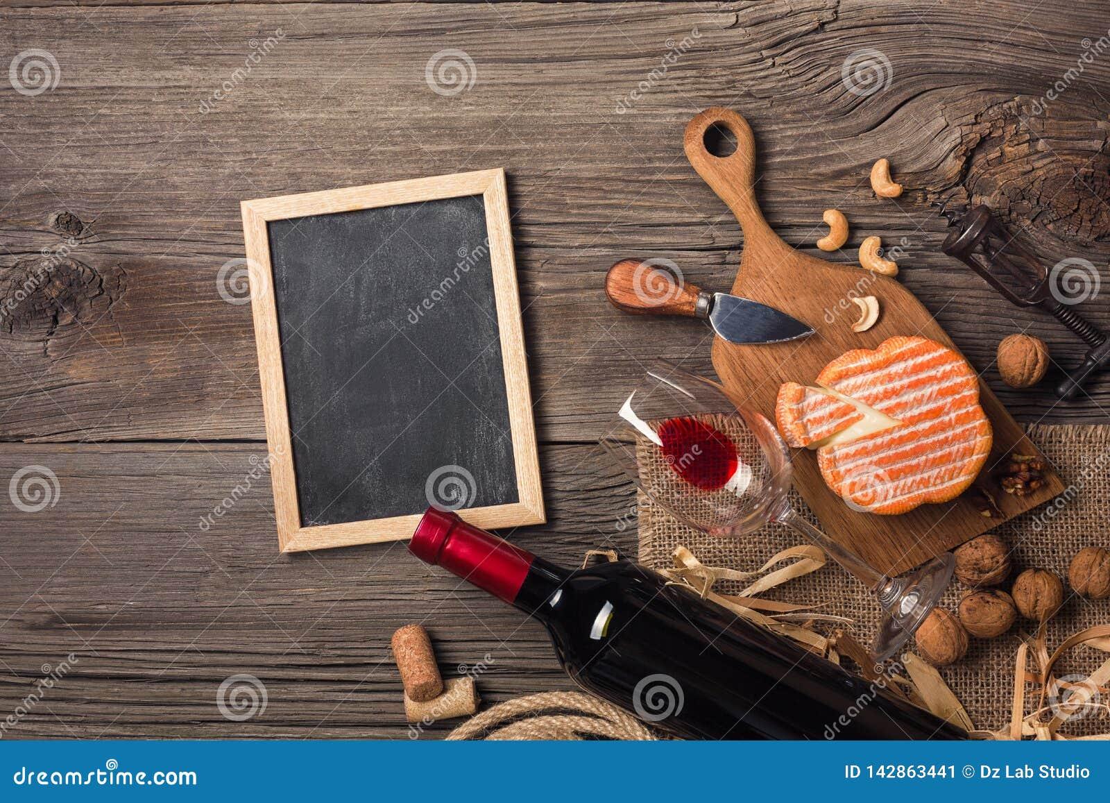 Κόκκινο κρασί σε ένα κιβώτιο με ένα τυρί γυαλιού, ανοιχτήρι και κρέμας σε έναν ξύλινο παλαιό πίνακα