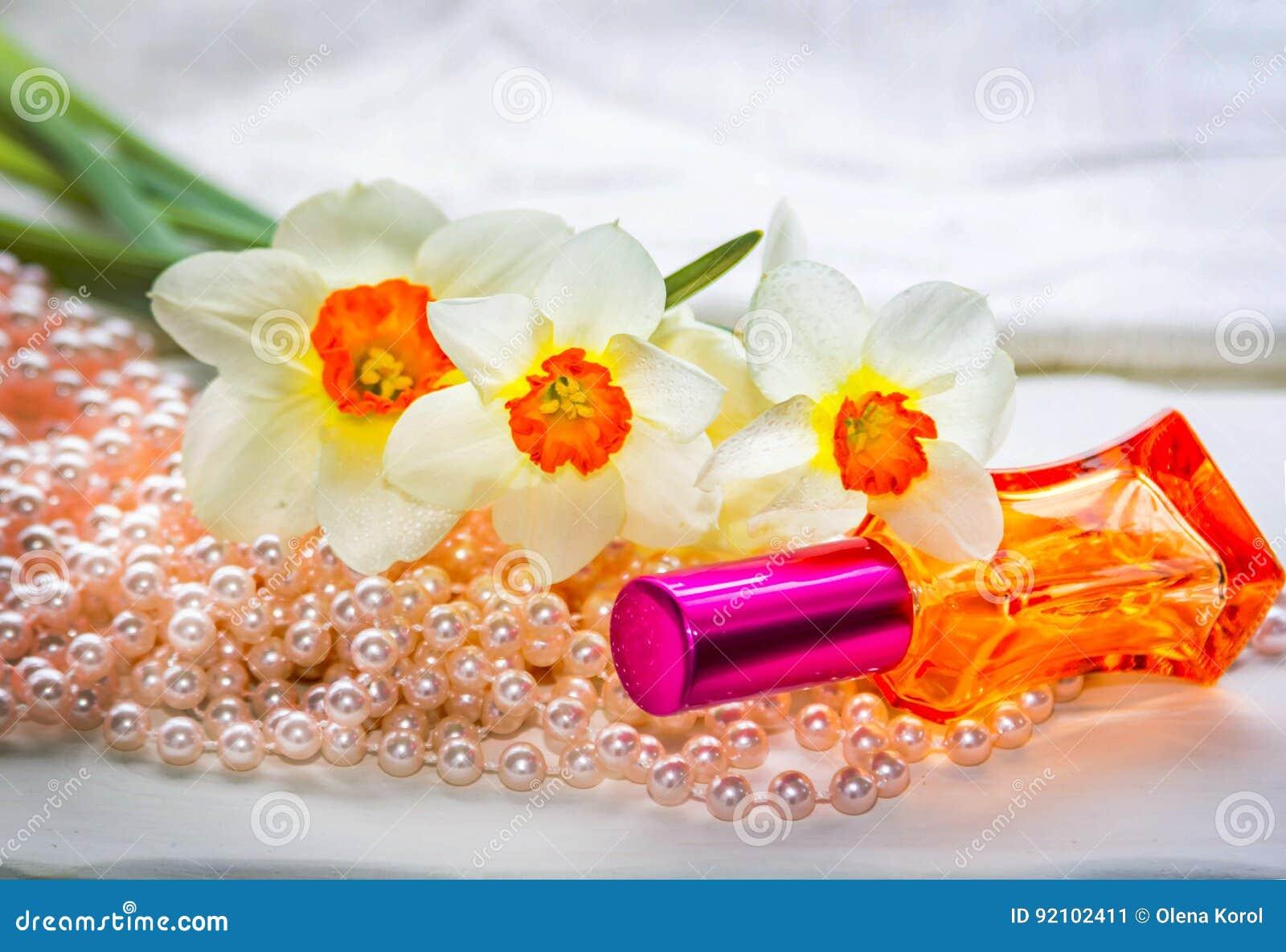 Κόκκινο μπουκάλι αρώματος γυαλιού, χάντρες μαργαριταριών και daffodil λουλούδια
