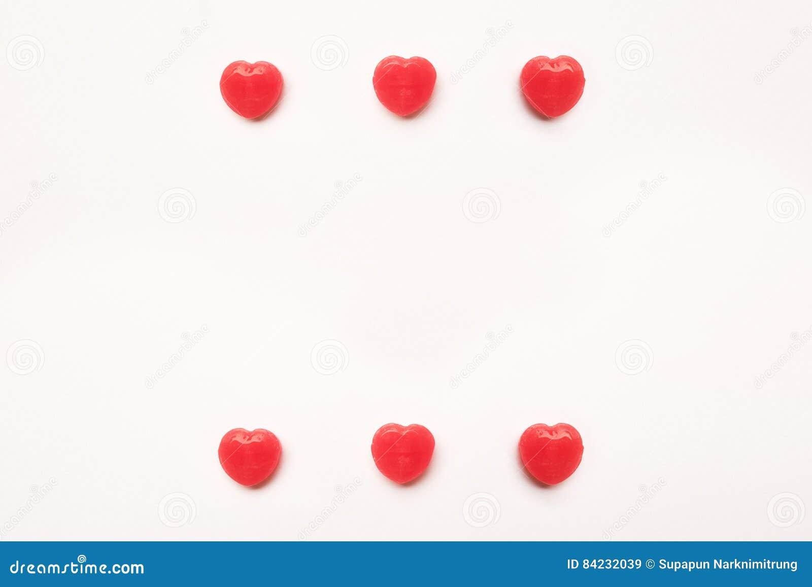 Κόκκινο σχέδιο καραμελών μορφής καρδιών ημέρας βαλεντίνων ` s στο κενό υπόβαθρο της Λευκής Βίβλου άνδρας αγάπης φιλιών έννοιας στ