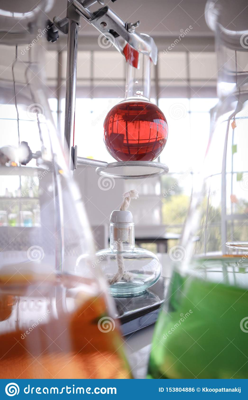 Κόκκινο υγρό στη φιάλη δοκιμής γυαλιού στο ράφι Θέση λαμπτήρων Alcolhol κάτω με το θολωμένο πορτοκαλί και πράσινο χημικό εργαστηρ