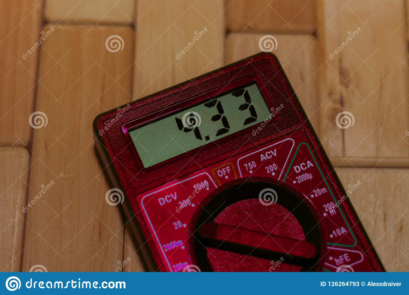 Κόκκινο ψηφιακό μετρώντας πολύμετρο στο ξύλινο πάτωμα Παρουσιάζει 4 33V ή πλήρως φορτισμένη μπαταρία Περιλαμβάνει το βολτόμετρο,