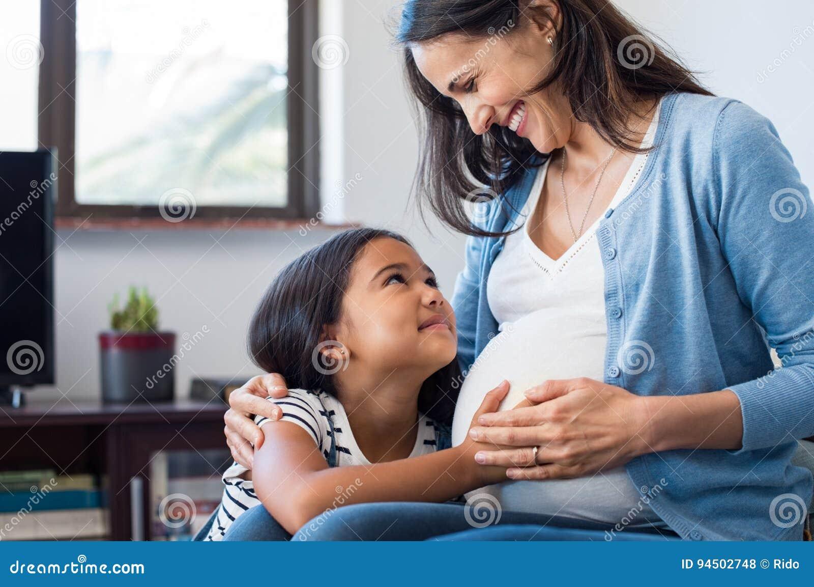 Κόρη σχετικά με την κοιλιά της έγκυου μητέρας της