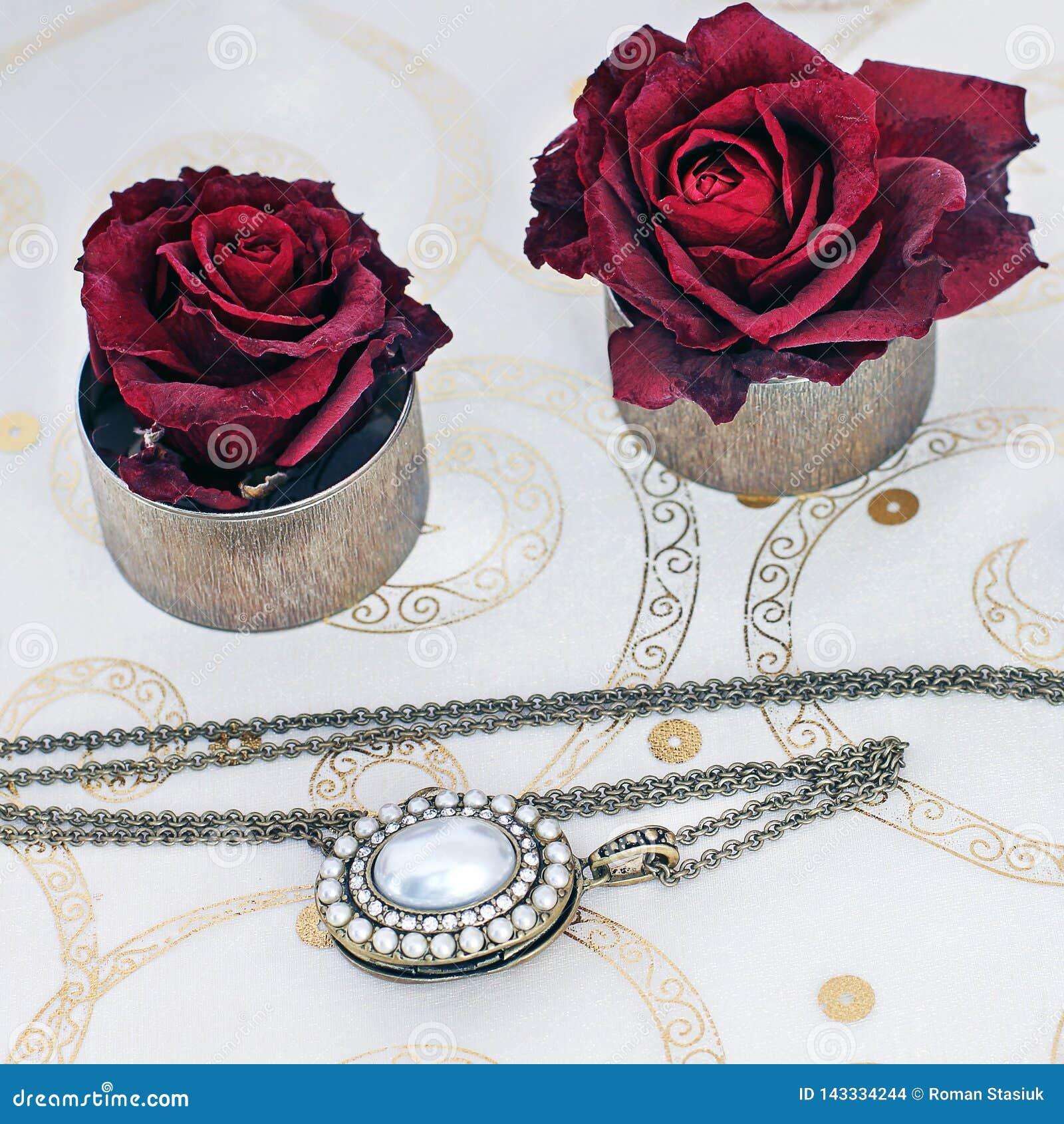 Κόσμημα και λουλούδια Περιδέραιο και κόκκινα τριαντάφυλλα
