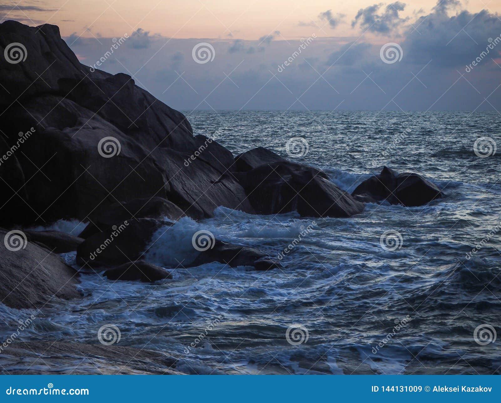 Κύματα που συντρίβουν στις παράκτιες πέτρες στην ανατολή