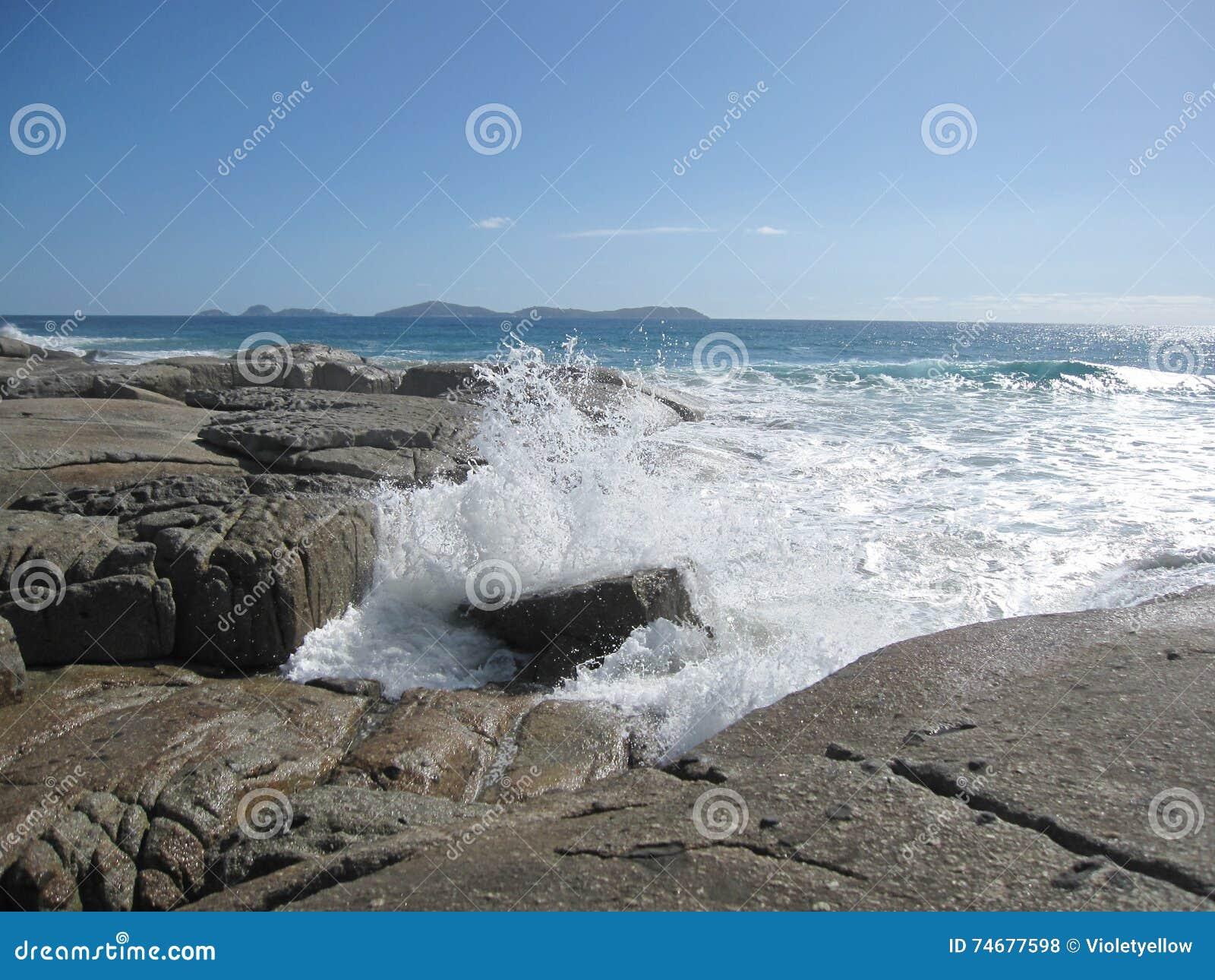 Κύμα που χτυπά την αυστραλιανές δύσκολες ακτή και την παραλία με τους γιγαντιαίους βράχους