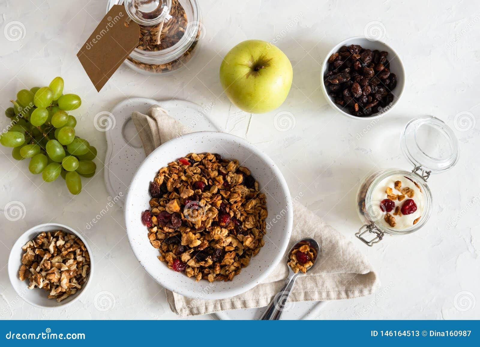 Κύπελλο του σπιτικού granola με τα καρύδια και τα φρούτα στο άσπρο υπόβαθρο λινού r Υγιές πρόγευμα, να κάνει δίαιτα, διατροφή