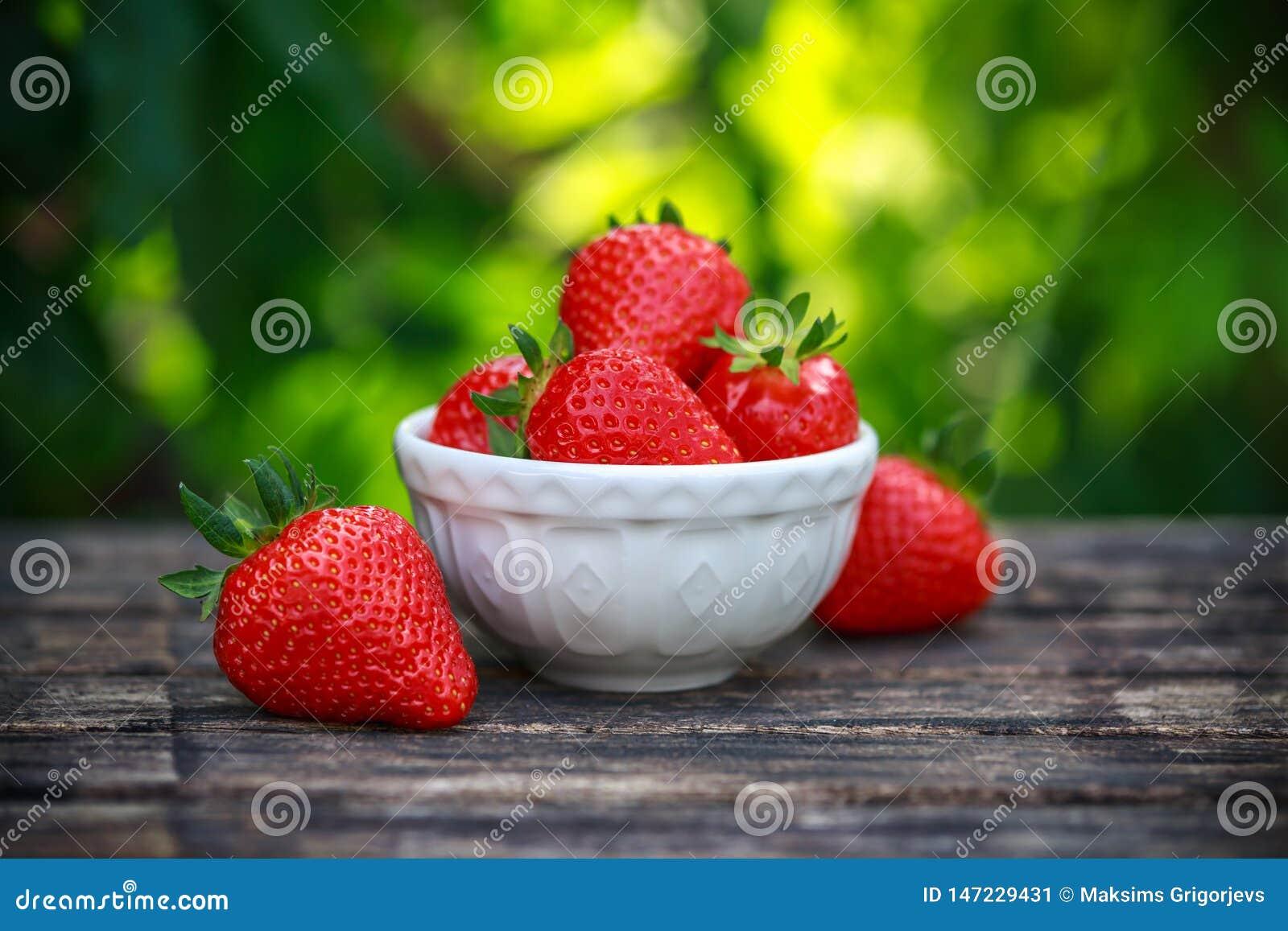 Κύπελλο των φρέσκων φραουλών στον ξύλινο πίνακα στο θερινό κήπο