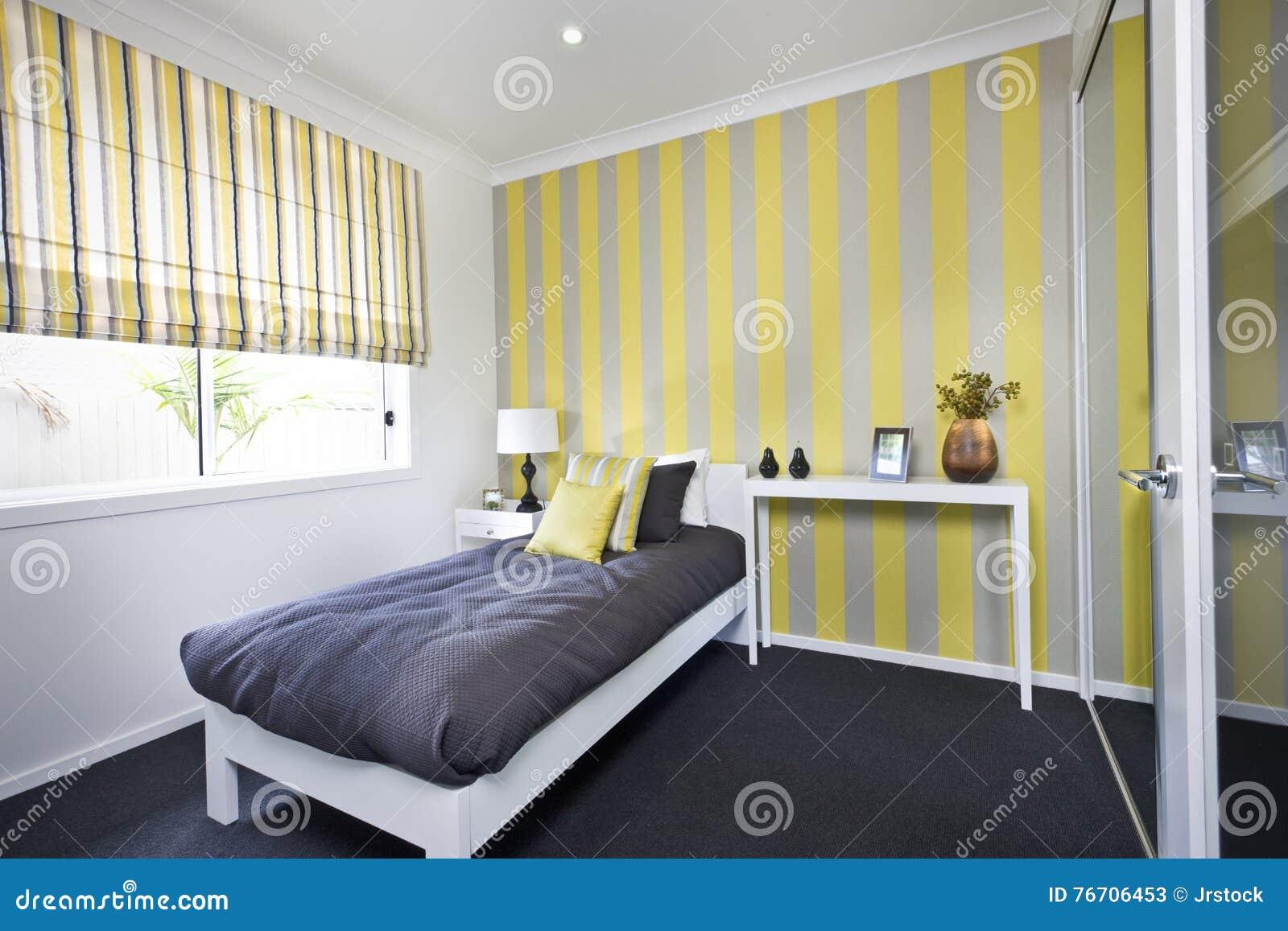 Κλασική κρεβατοκάμαρα με ένα μικρό κρεβάτι και μαξιλάρια εκτός από τα παράθυρα