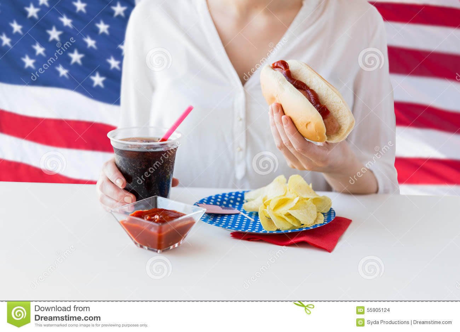 Κλείστε επάνω της γυναίκας που τρώει το χοτ-ντογκ με το κόκα κόλα