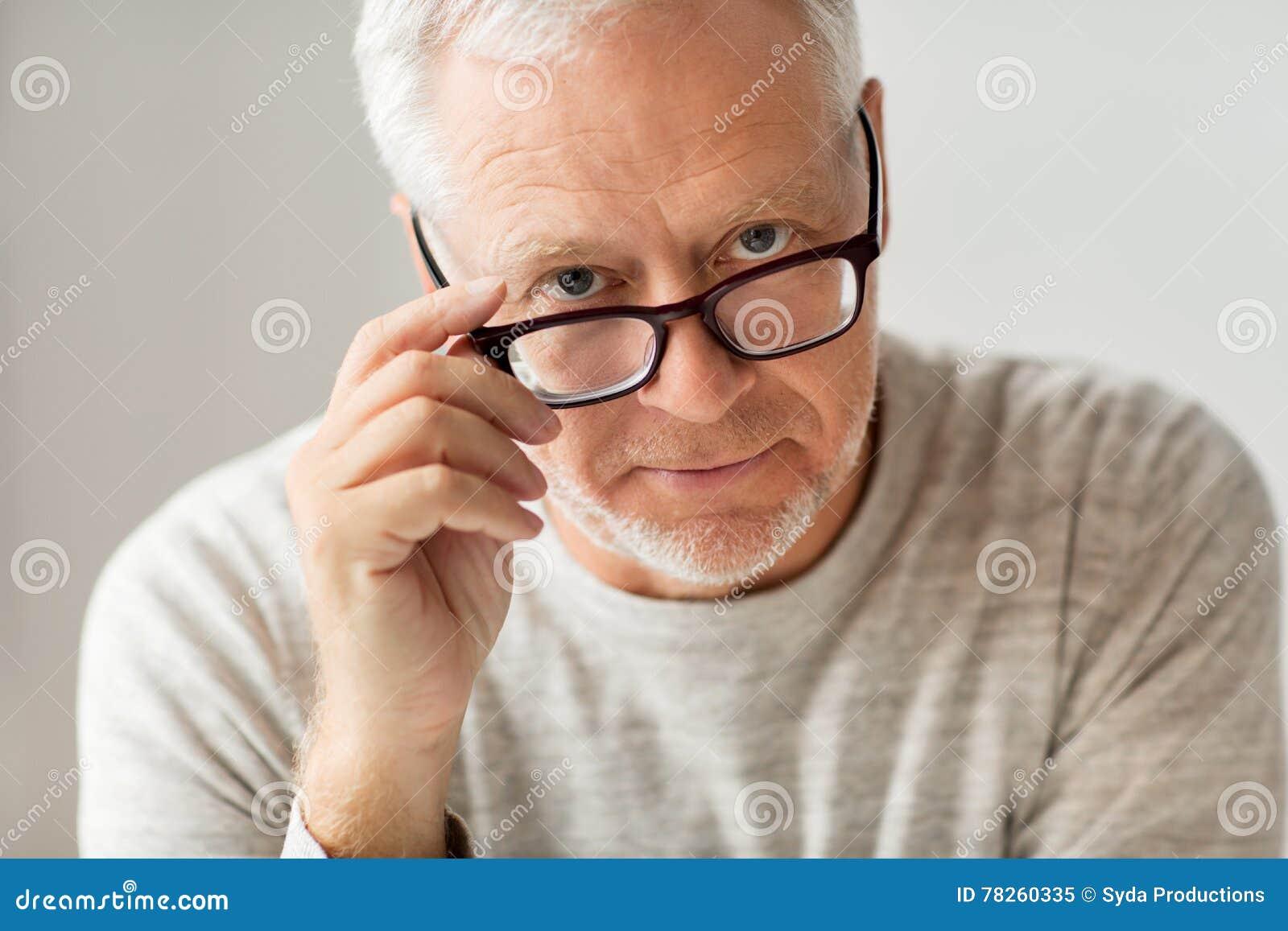 Κλείστε επάνω του ανώτερου ατόμου στη σκέψη γυαλιών