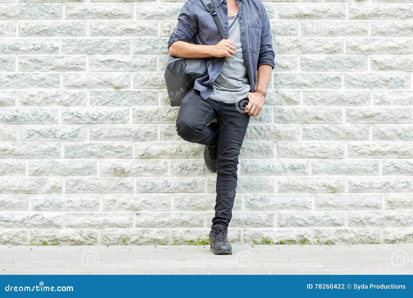 Κλείστε επάνω του ατόμου με το σακίδιο πλάτης που στέκεται στον τοίχο