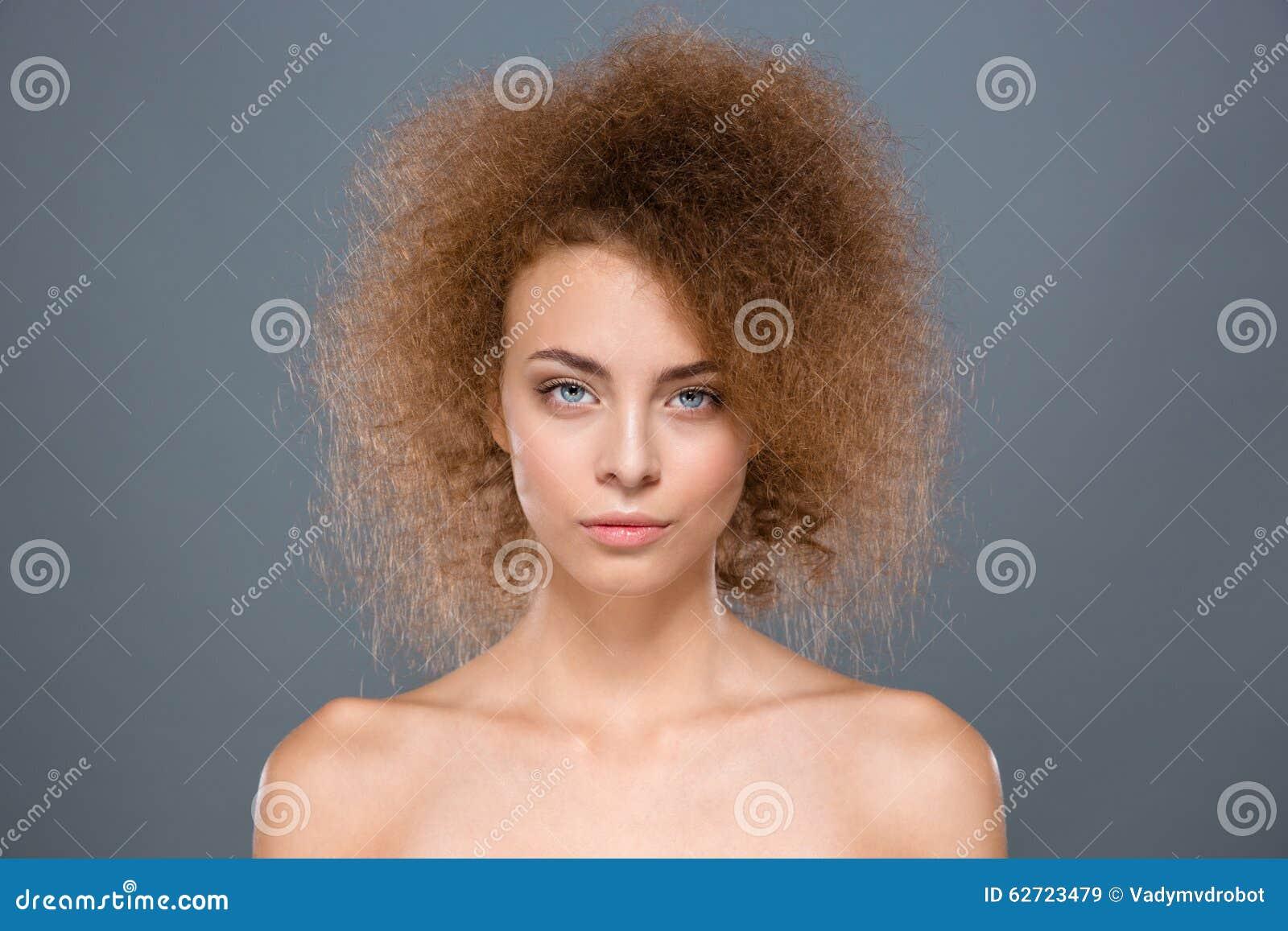 Κλείστε επάνω του ελκυστικού θηλυκού προτύπου μόδας με τη σγουρή τρίχα