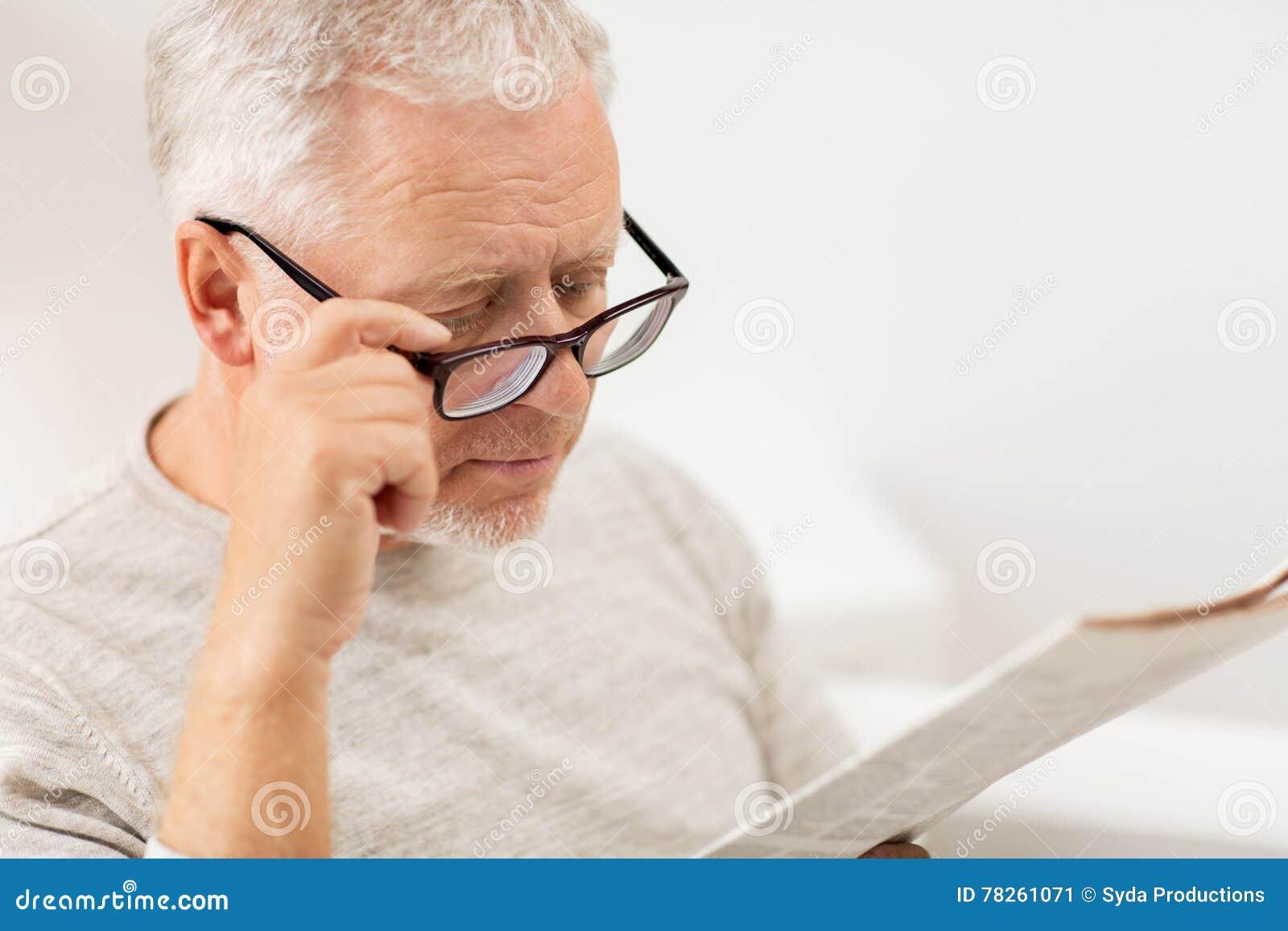 Κλείστε επάνω του ηληκιωμένου στα γυαλιά που διαβάζει την εφημερίδα