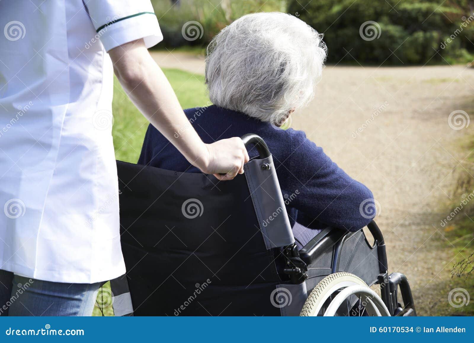 Κλείστε επάνω του φροντιστή που ωθεί την ανώτερη γυναίκα στην αναπηρική καρέκλα