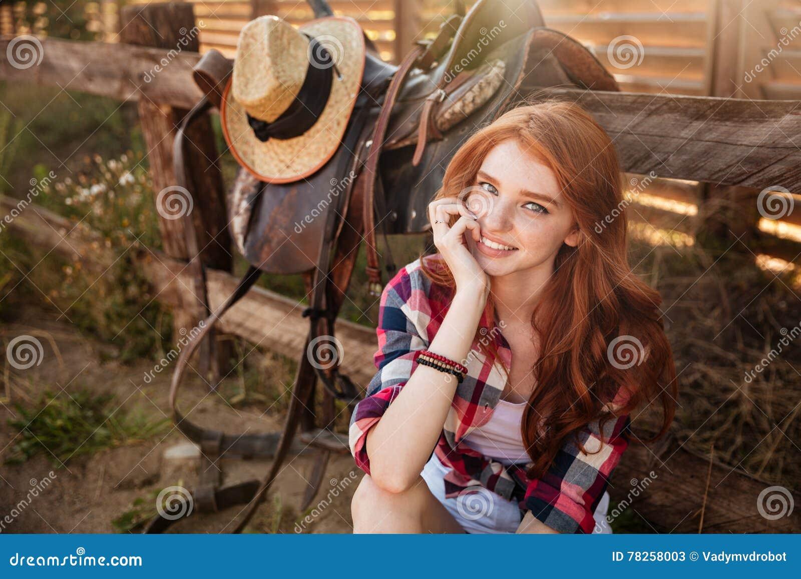 Κλείστε επάνω το πορτρέτο μιας ευτυχούς όμορφης redhead στήριξης cowgirl